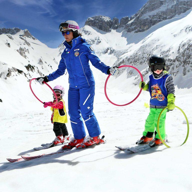Maestra di sci mentre insegna a sciare a bambini